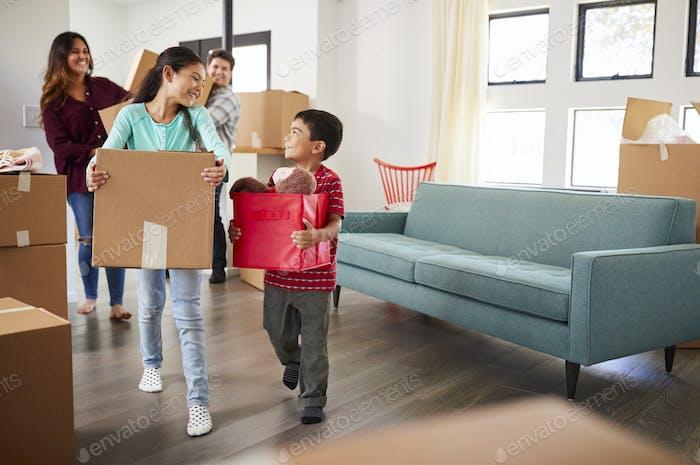 Excited Family Carrying Boxes Into New Home On Moving Day