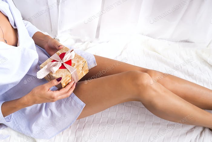 girl on the bed holds a gift