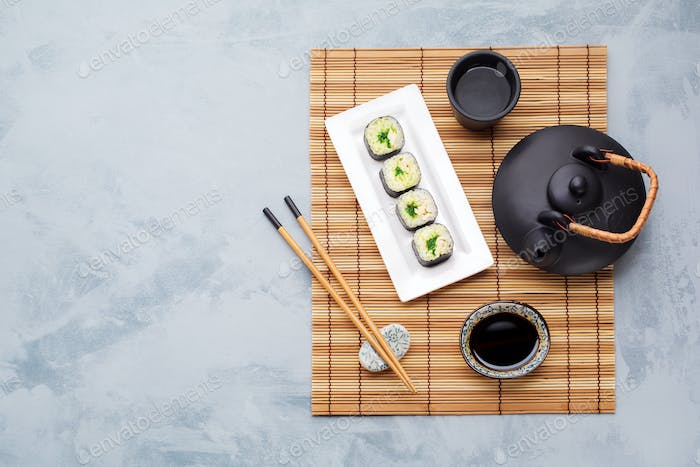 Teapot, green tea, sushi and soy sauce.