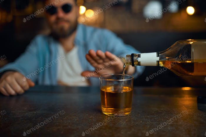 Man in sunglasses refuses to drink alcohol