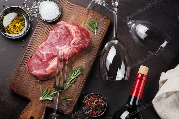 Raw ribeye beef steak cooking with ingredients