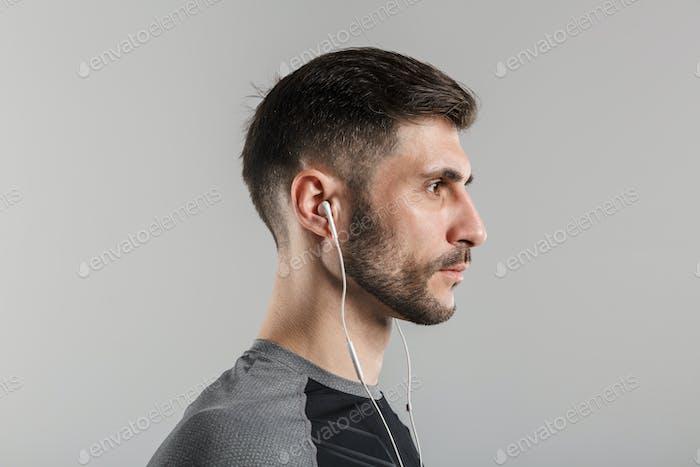 Image in profile of brutal unshaven sportsman using earphones