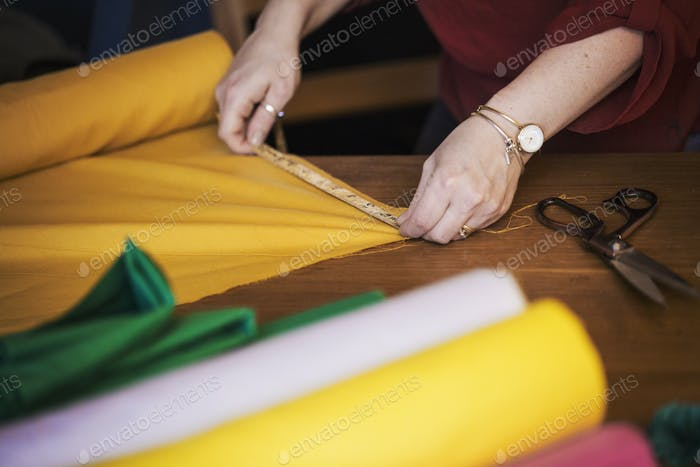 A woman using a tape measure to measure yellow fabric for cutting out.