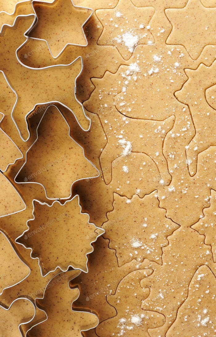 Christmas cookie cutters over gingerbread dough
