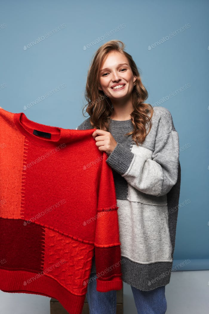 Young beautiful smiling woman in gray sweater holding red sweater in hands happily looking in camera