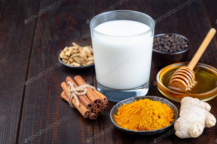 Ingredients for turmeric moon milk on wooden background, horizontal, copy space