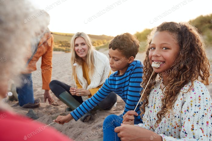 Portrait Of Multi-Generation Family Toasting Marshmallows Around Fire On Winter Beach Vacation