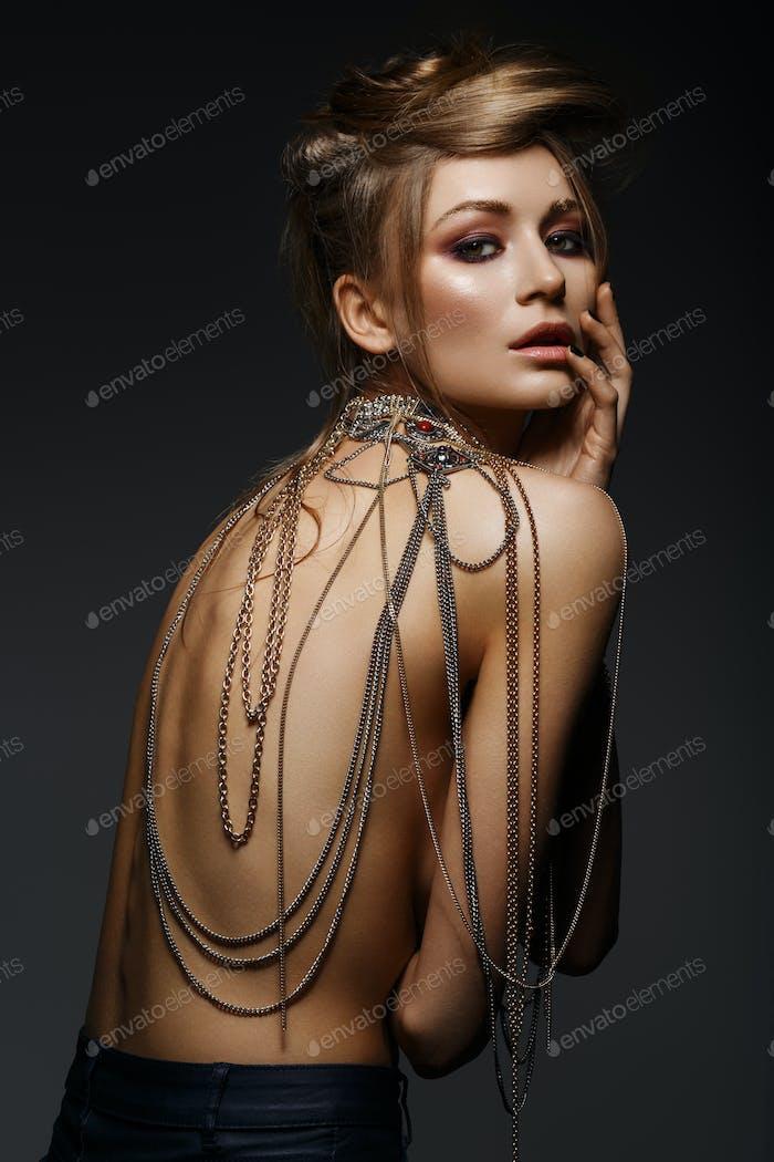 schönes Mädchen mit vielen goldenen und bronzefarbenen Ketten