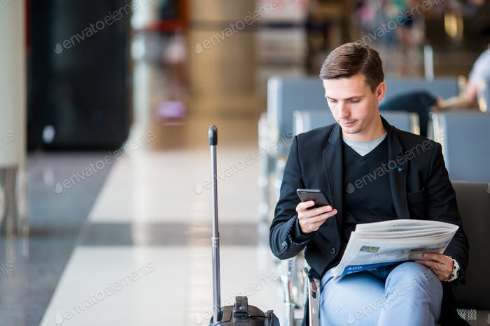 Passenger in an airport lounge waiting for flight aircraft. Young man with cellphone in airport