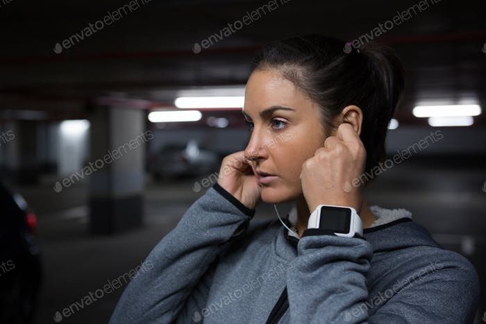 Fit woman listening to music in underground parking area