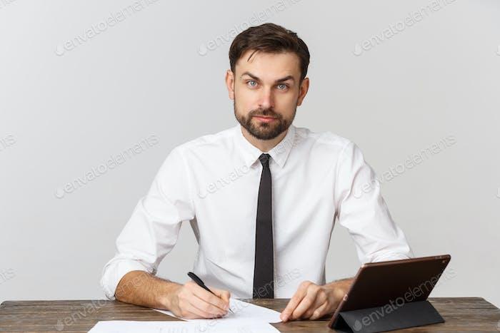 Eine Ansicht eines geschäftigen Geschäftsmannes, der ein Dokument im Büro vor weißem Hintergrund unterschreibt