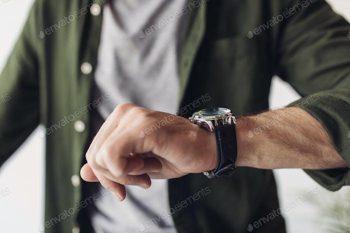 Cropped shot of man in shirt checking wristwatch indoors