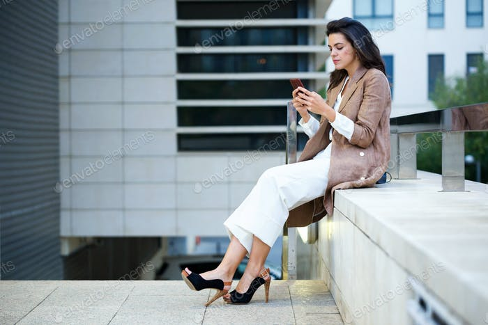 Beautiful young businesswoman texting with her mobile phone in the street.