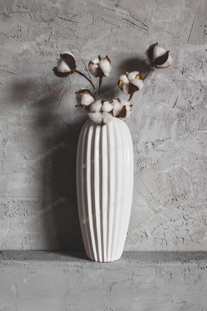 Zweige aus Baumwolle in einer Vase auf einem Hintergrund
