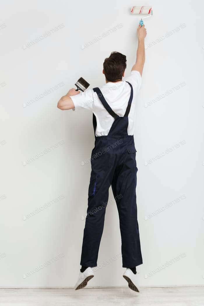 Full length back view of young male builder painting wall