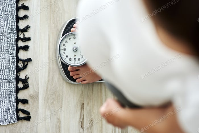 Horizontal image of woman standing on a bathroom scale