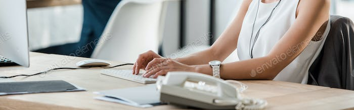 panoramic shot of woman in typing on computer keyboard in office