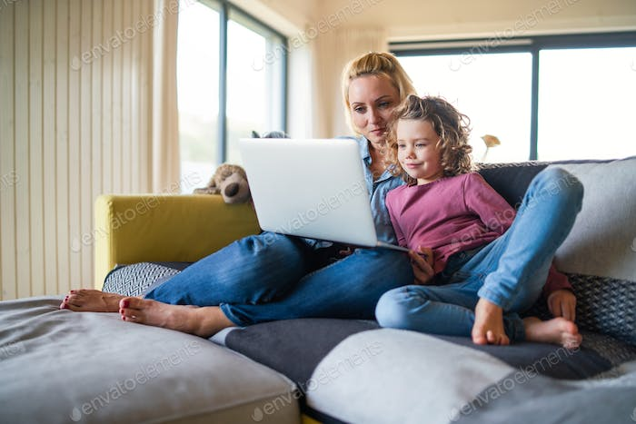 A cute small girl with mother on sofa indoors at home, using laptop
