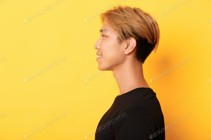 Profile of stylish handsome asian guy with fair hair looking left and smiling, standing over yellow