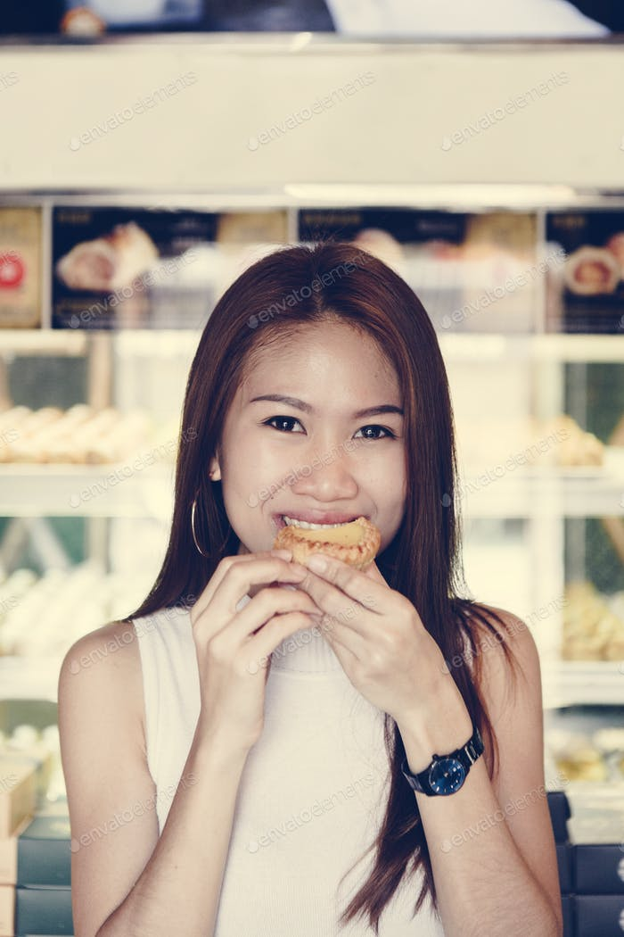 Asian girl having a bite of tart
