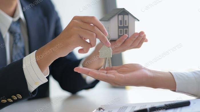 Nahaufnahme Aufnahme von Immobilienmakler liefert Bauschlüssel an Kunden.