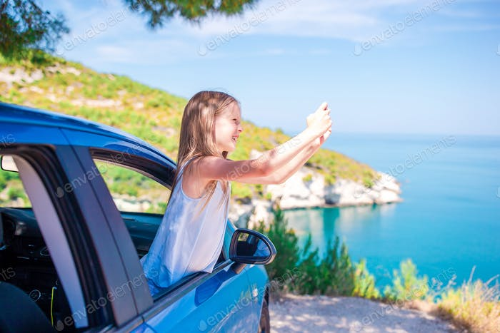 Little girl on vacation travel by car background beautiful landscape