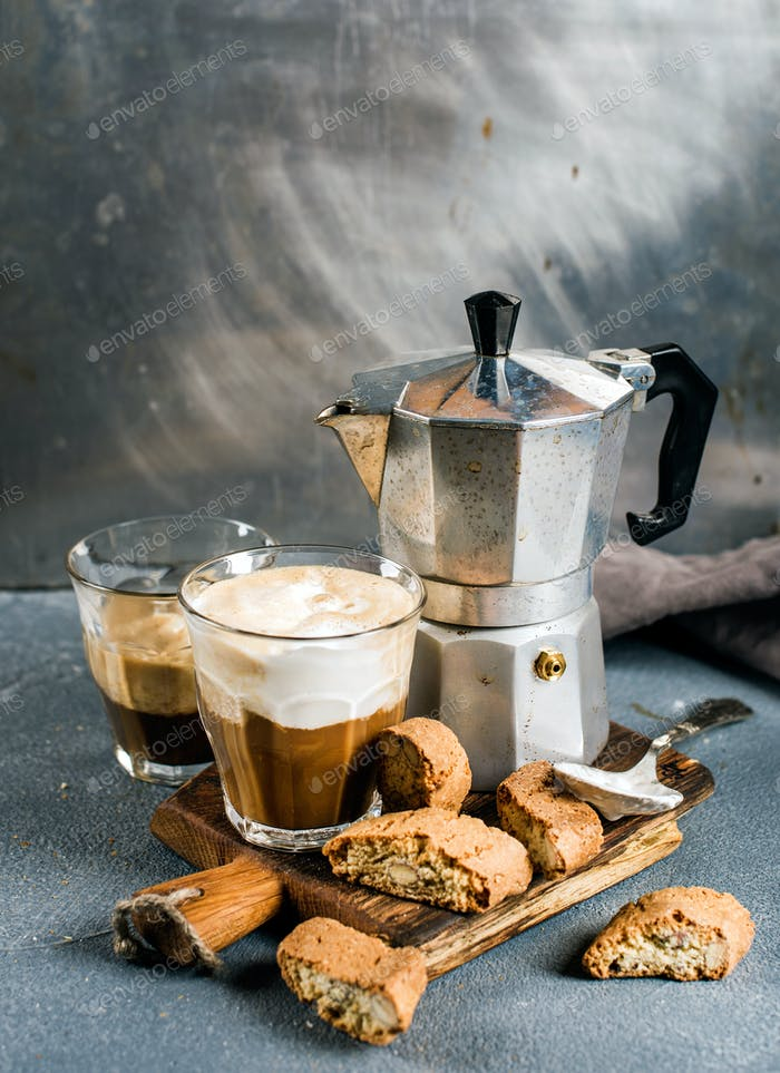Glass of latte coffee on rustic wooden board, cantucci biscuits and steel Italian Moka pot