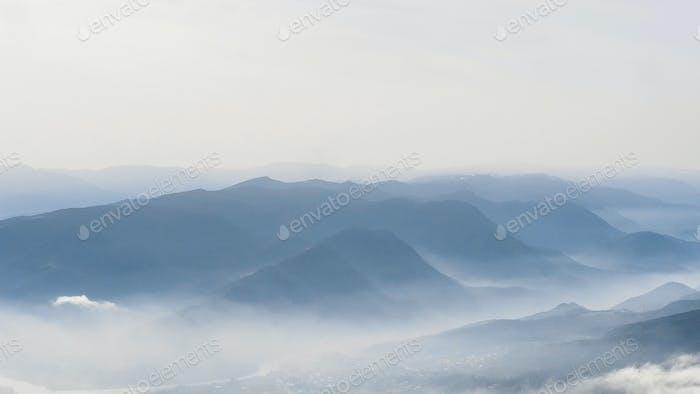 malerischer Blick auf die Berge bei Nebel und Himmel