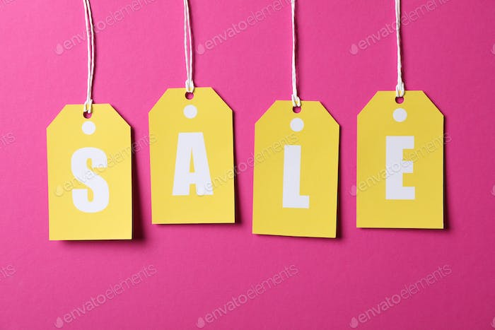 Inscription Sale on price tags on pink background. Black Friday concept