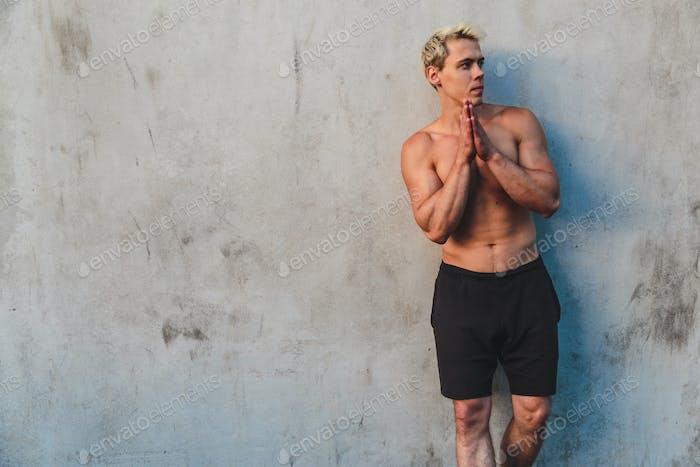Natürliches Porträt junger athletischer hemdloser Mann, der in der Nähe von Betonwand steht.