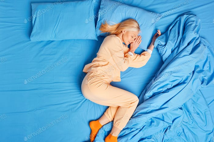 Peaceful blonde woman pensioner sleeps on side in cozy bed has healthy sleep and good rest dressed i
