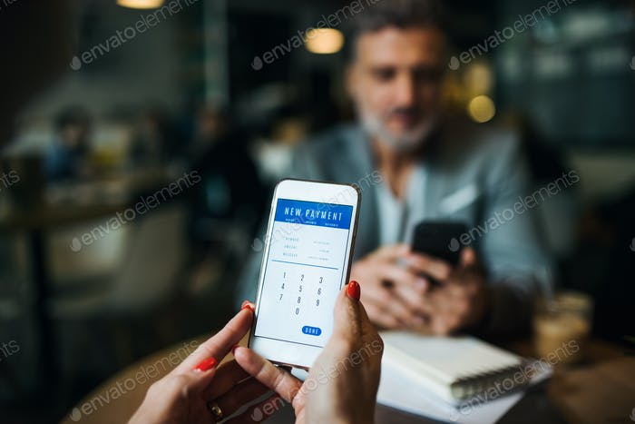 Midsection of businesspeople with smartphone in a cafe, checking finances