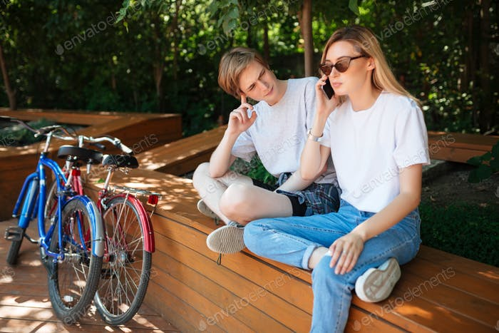 Tired man sitting and thoughtfully looking at girl with blond hair that talking on her cellphone