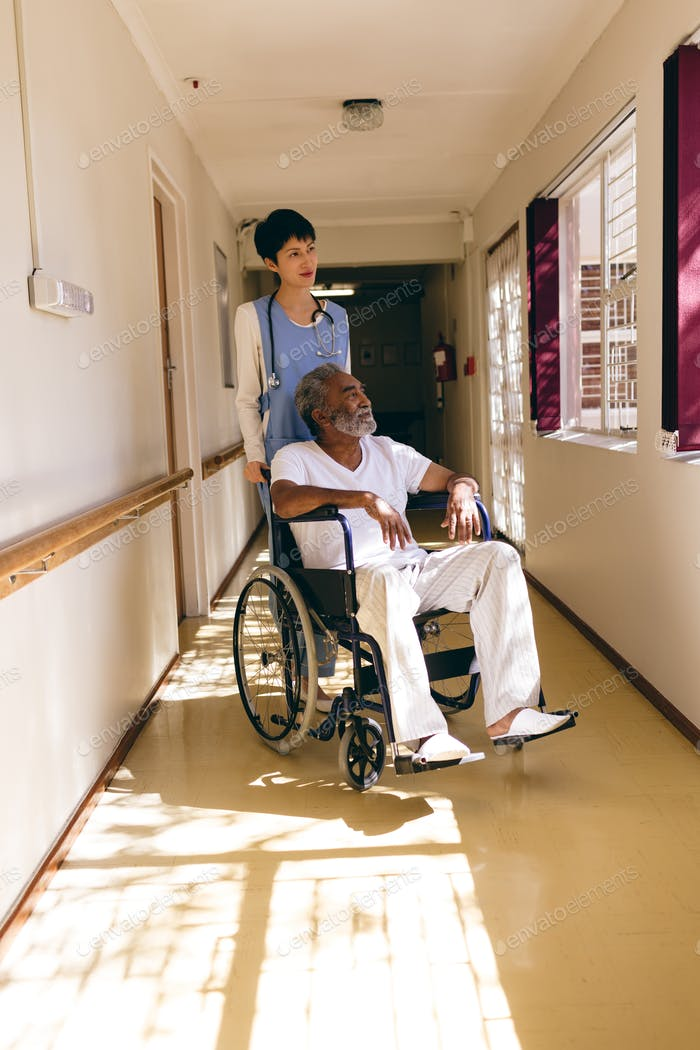 Female nurse standing while senior male sits in wheelchair in corridor at retirement home.