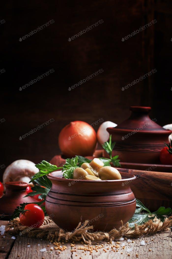 Homemade pickled mushrooms champignons in earthenware bowl
