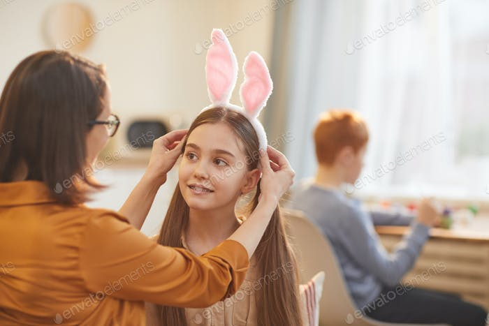 Mother making rabbit costume for her daughter