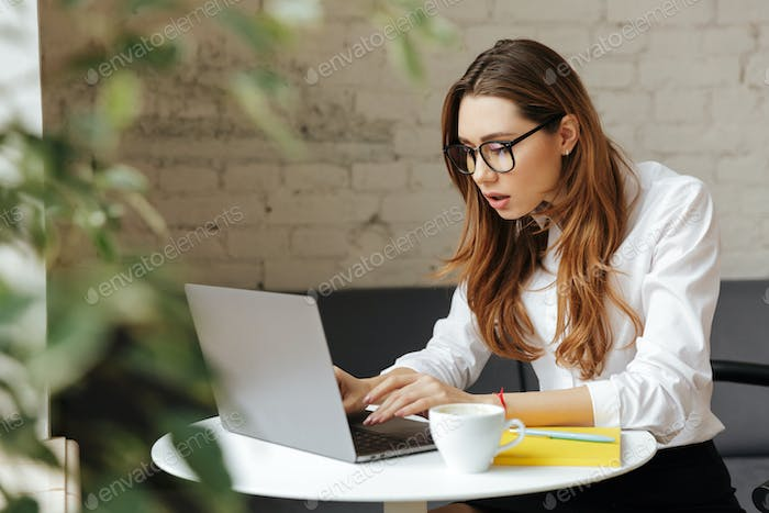 Confused business lady indoors using laptop