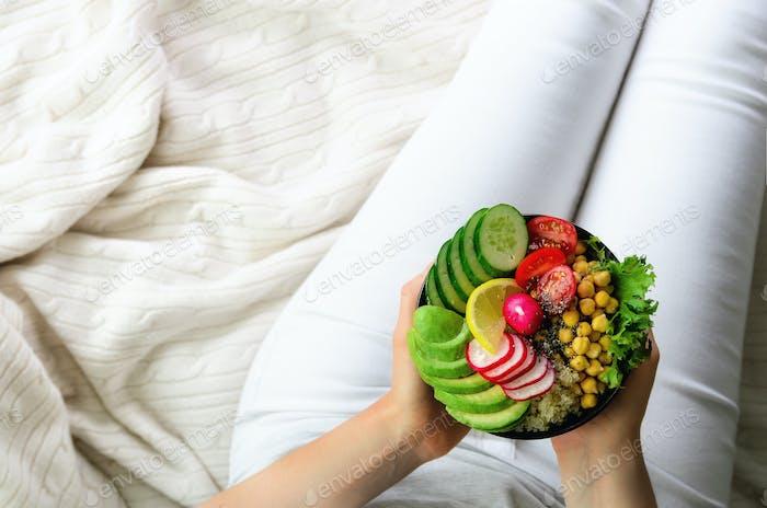Mädchen hält in den Händen Vegan, Detox Raw Buddha Schüssel mit Avocado, Quinoa, Gurke, Rettich, Salat