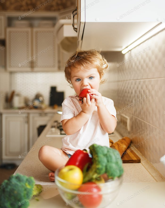 Little girl sitting on the table and eats tomato