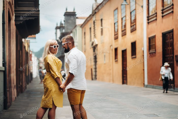 a modern married couple of lovers strolling in the old town of the island of Tenerife, a couple of