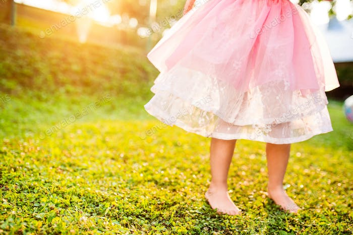 Unrecognizable girl in princess skirt running in sunny garden