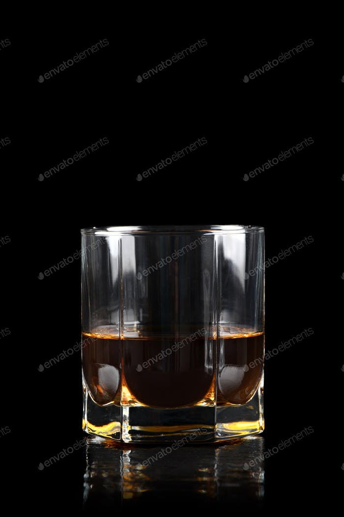 Glass of whiskey on black background