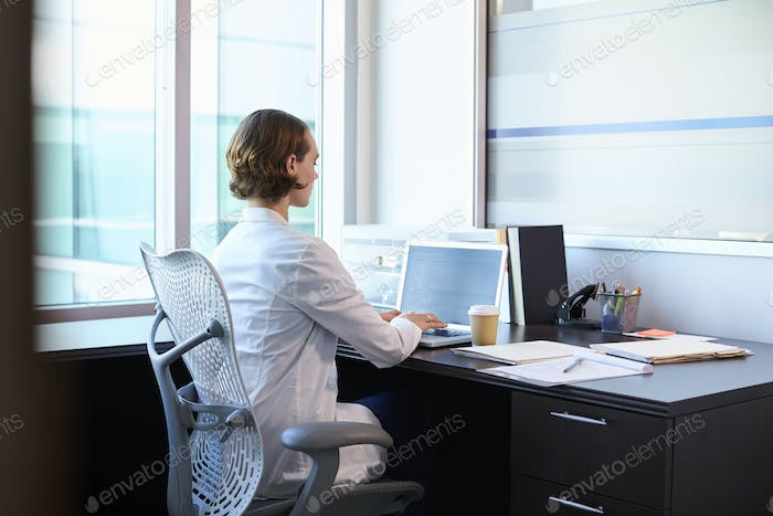 Female Doctor Wearing White Coat In Office Working At Desk