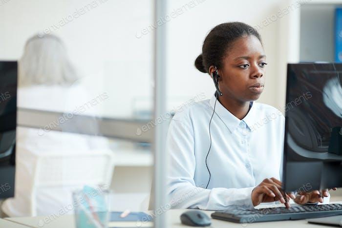 Afrikanische Geschäftsfrau trägt Headset am Arbeitsplatz
