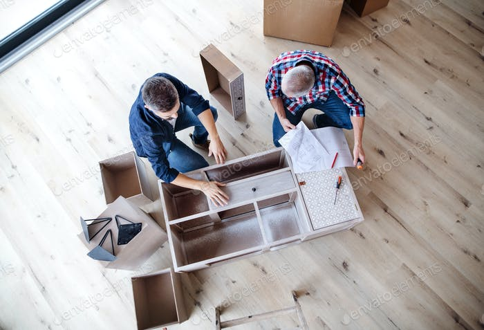 A top view of man with his senior father assembling furniture, a new home concept.