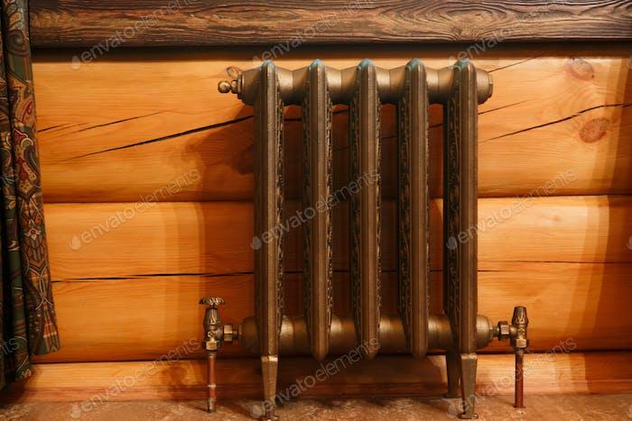Cast iron retro design radiator in timber house.