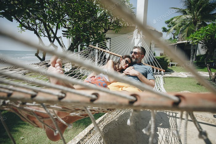 Couple relaxing in a hammock by the beach