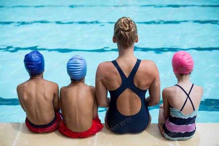 Female instructor teaching children at poolside