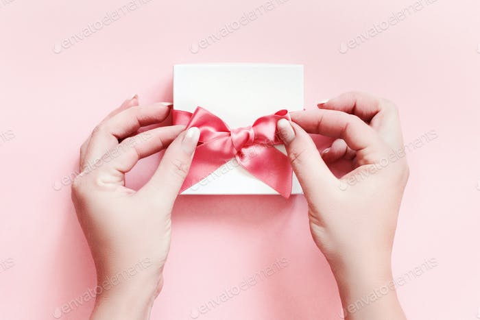 Hands tying a bow on a white gift box