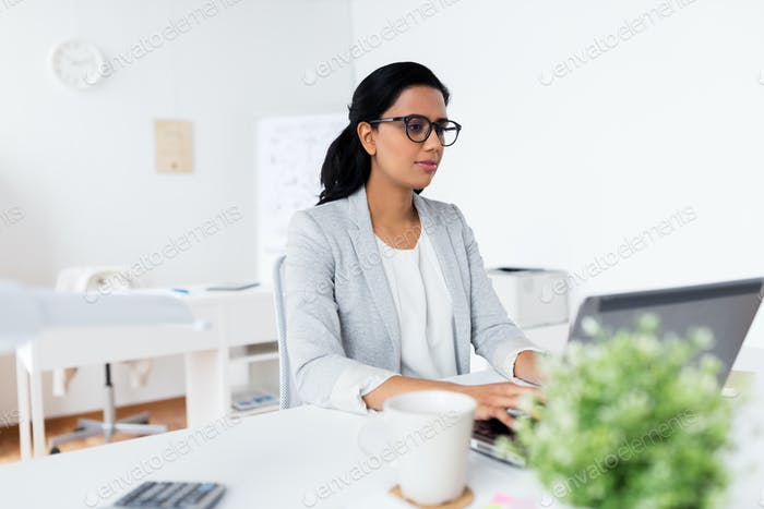 happy businesswoman with laptop at office